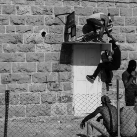 Palestinian protestors gathering behind a house close to where the clashes are taking place