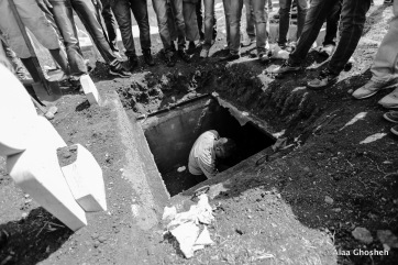 A relative of Muhammad cleans his grave at the family cemetery in Shu'afat