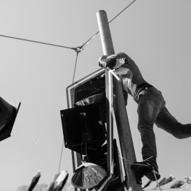 A man climbing a traffic light pole to kick off the traffic lights one by one
